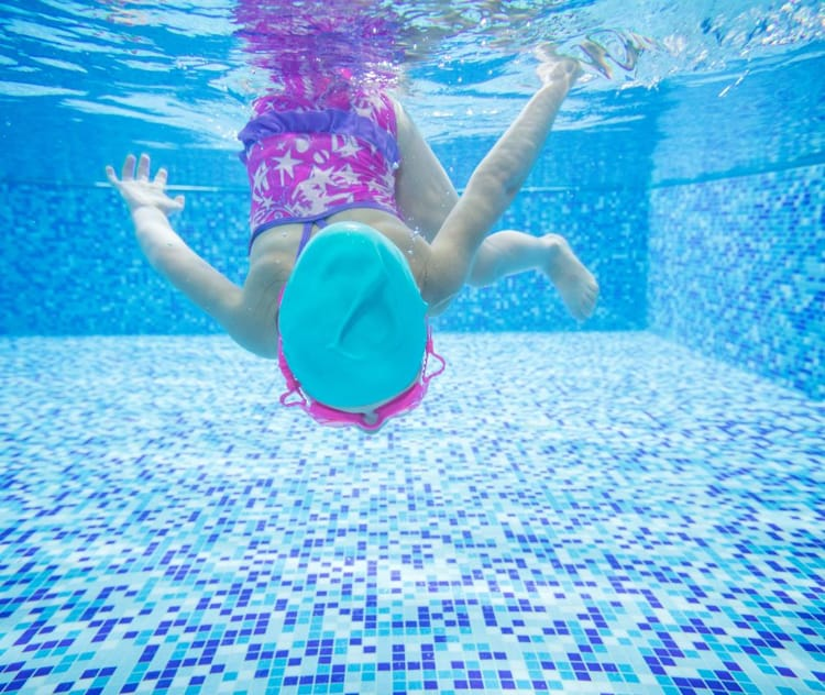 little-girl-diving-in-swimming-pool-PBVA7DU